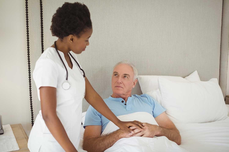Nurse Helping Man in Bed